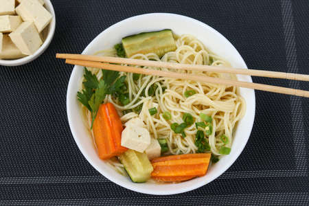 Traditional asian soup with tofu cheese, noodles, carrots and zucchini on dark background, This dish usually contains bouillon and vegetables, Top view, Closeup