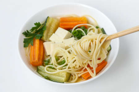 Traditional asian soup with tofu cheese, noodles, carrots and zucchini on white background, dish usually contains bouillon and vegetables, Horizontal orientation, Closeup