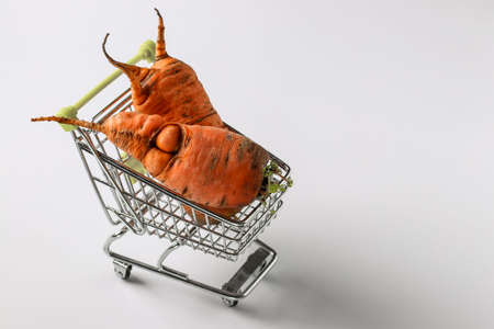 Grocery trolley with ugly carrot on white background. Concept environmental shopping, Organic food, Copy space Foto de archivo