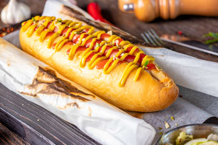Hot dog with sausage is located on a wooden board against a dark background, rustic style, Horizontal orientation, Closeup