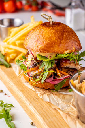 Vegetarian fresh burger with mushrooms and vegetables, served with french fries on a wooden board, healthy fast food, Closeup, Vertical orientation Zdjęcie Seryjne