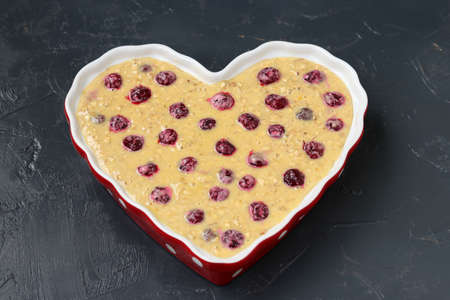 Dough for oatmeal pie with cherries in ceramic form in the shape of a heart on a dark background, Top view, Closeup