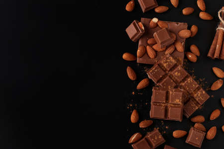 Chocolate with almonds and cinnamon on a dark background close-up, Copy space