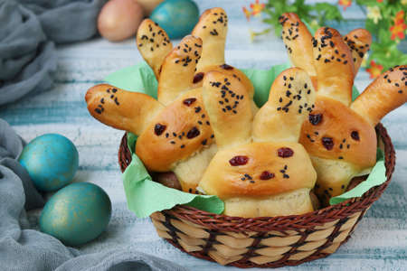 Easter Buns in the form of hares with multi-colored eggs are located in a wicker basket on a blue background, culinary idea for children, Closeup Standard-Bild - 142185593