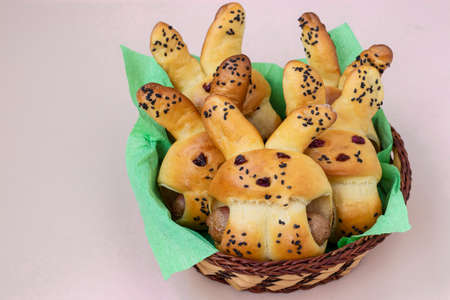 Easter Buns in the form of hares are located in a wicker basket on a light background, culinary idea for children, Closeup Standard-Bild - 142194950