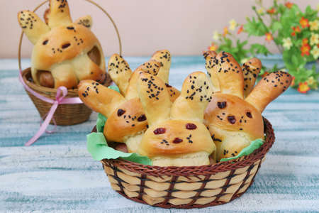 Easter Buns in the form of hares are located in a wicker baskets on a blue background, culinary idea for children, Closeup Standard-Bild - 142328911