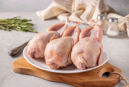 Three raw fresh quails on a white plate on a wooden board, Closeup, gray background