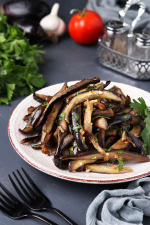 Fried eggplants with garlic and soy sauce, sliced in stripes, in a plate on a dark background, Vegetarian menu, Vertical format