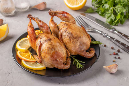 Baked quails with lemon and orange served on a dark plate on a gray background, Closeup Standard-Bild
