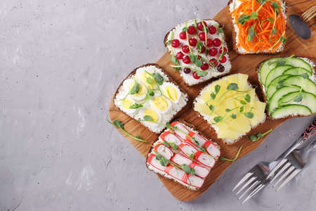 Six sandwiches on toast with fresh carrots, cucumbers, pineapple, red currant, crab sticks and quail eggs with peas microgreens on wooden board on gray background, View from above, Copy space Reklamní fotografie