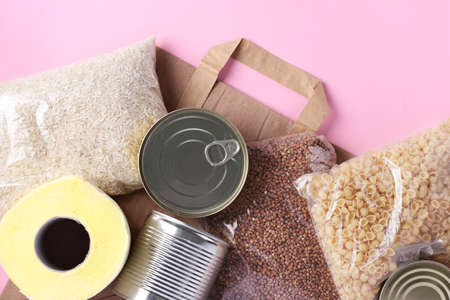 Paper bag with food supplies crisis food stock for quarantine isolation period on pink background. Rice, buckwheat, pasta, canned food, toilet paper. Food delivery, Donation, Top view, Closeup