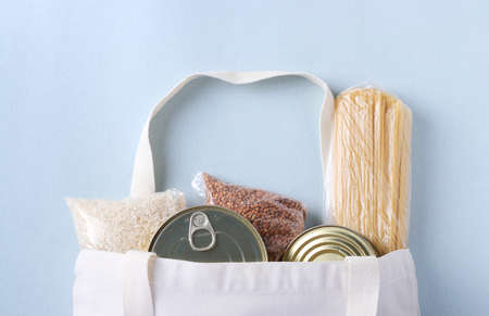 Textile Grocery Bag with food supplies crisis food stock for quarantine isolation period on light blue background. Rice, buckwheat, pasta, canned food. Food delivery, Donation, Top view