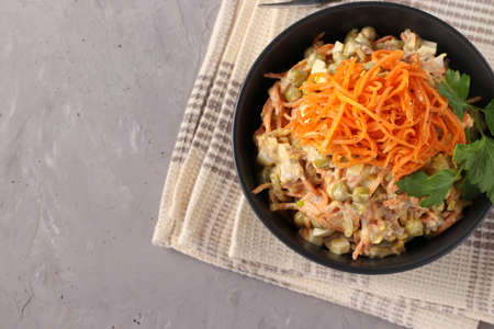 Salad with Korean carrots, meat and canned peas in a dark bowl on a gray background, Closeup, Top view