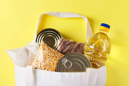 Food delivery, Donation. Textile Bag with food supplies crisis food stock for quarantine isolation period on yellow background. Rice, buckwheat, peas, canned food, vegetable oil, Top view