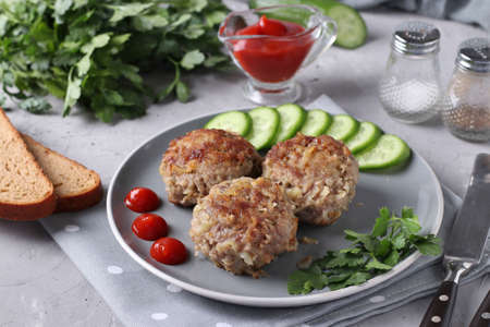 Beef cutlets served with cucumber and tomato sauce on a gray plate on gray concrete background, Horizontal format