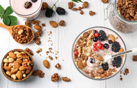 Granola crispy honey muesli with natural yogurt, berries, chocolate and nuts in a bowl against a light background, top view, horizontal format Zdjęcie Seryjne
