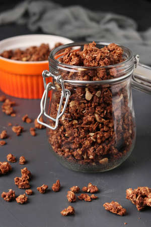 Granola crispy muesli with natural honey, chocolate, nuts in a glass jar and bowl against a dark background, vertical format, Closeup