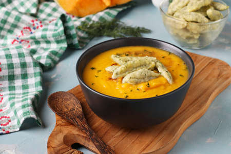 Pumpkin cream soup with cheese dumplings in dark bowl on light blue background, Horizontal format, Closeup