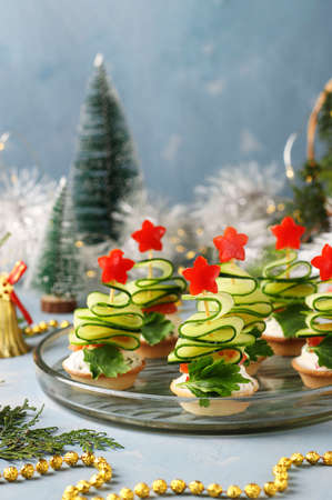 Festive canapes in the shape of Christmas trees made of cucumbers and stars of bell pepper on a light blue background with two glasses of wine, Vertical format Foto de archivo
