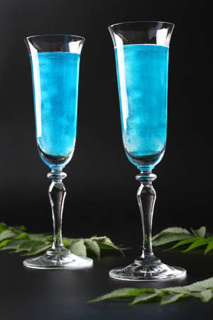 Shimmer edible glitter sparkling blue wine in two tall glasses on black background. Vertical format.