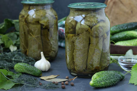 Canned cucumbers in grape leaves in jars on a dark background, Harvest for the winter