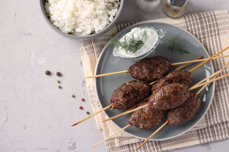 Kofta kebab on wooden skewers on a plate with sauce and a side dish of rice on the table, traditional dish of Arab cuisine, grilled minced meat shish kebab, Top view