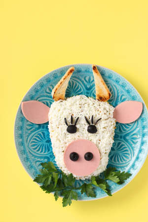 Festive Bull-shaped salad for 2021 on yellow background, Symbolic food for new year, Top view, Vertical format