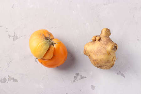 Ugly tomato and potato on light gray background, Closeup, Ugly food consept, Top view Stok Fotoğraf