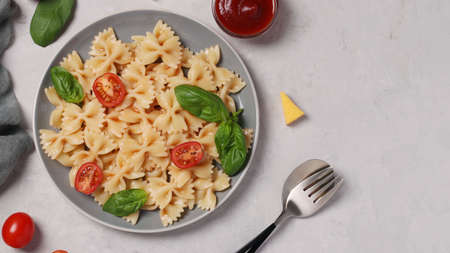 Farfalle pasta with cherry tomatoes, tomato sauce and basil on white background, Top view, Copy space