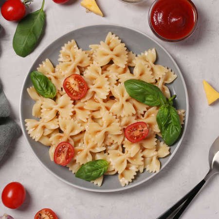 Farfalle pasta with cherry tomatoes, tomato sauce and basil on white background, close up, View from above