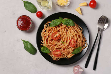 Spaghetti with tomato sauce and cherry tomatoes with basil on black plate on light background, View from above