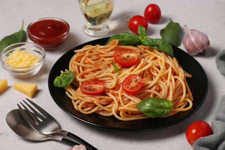 Spaghetti with tomato sauce and cherry tomatoes with basil on black plate on light background Stock fotó