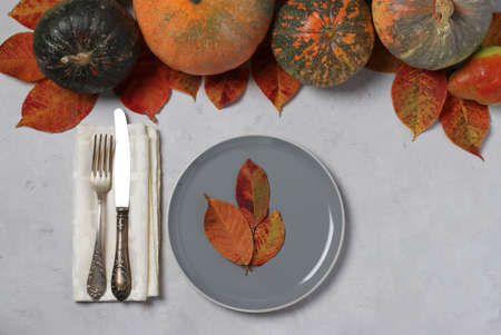 Table setting on Thanksgiving Day decorated pumpkin, pears and colorful leaves on grey. View from above