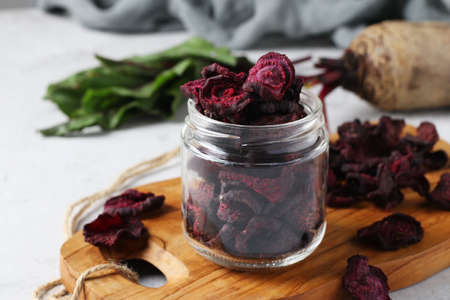 Beet chips in a glass jar on wooden board on light background. Closeup. Horizontal format