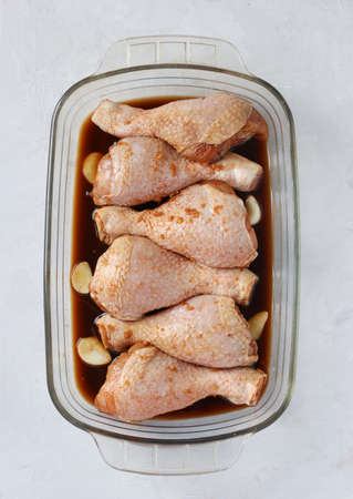 Raw chicken drumsticks in soy sauce with garlic in a mold before baking. Vertical format.