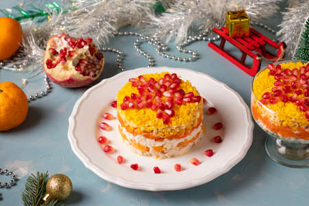 Festive New Year's salad with chicken, eggs, carrots and corn, decorated with a star of pomegranate seeds on light blue