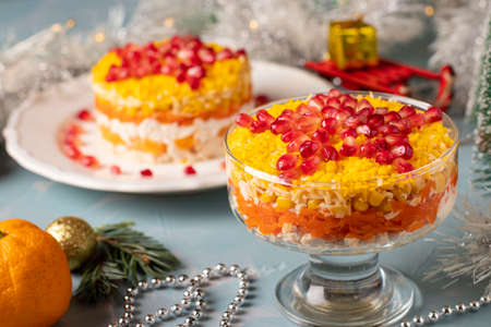 New Year's salad with chicken, eggs, carrots and corn, decorated with a star of pomegranate seeds on light blue