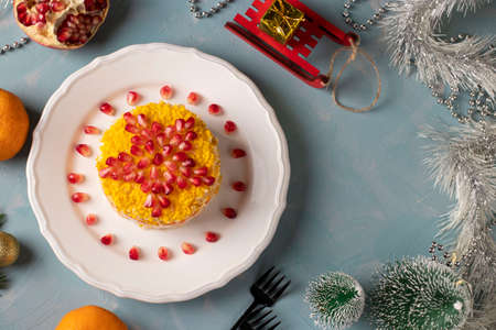 Festive New Year's salad with chicken, eggs, carrots and corn, decorated with a star of pomegranate seeds on white plate