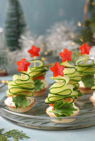 Festive canapes in the shape of Christmas trees made of cucumbers and stars bell pepper on light blue background, Closeup.