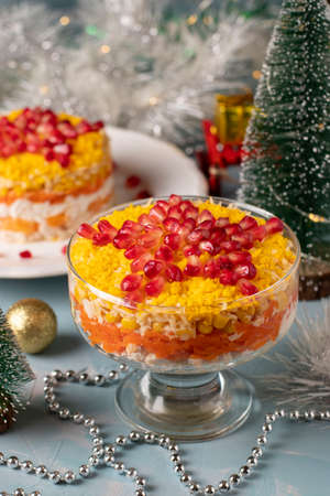 Festive New Year's salad with chicken, eggs, carrots and corn, decorated with a star of pomegranate seeds on light blue background, vertical format