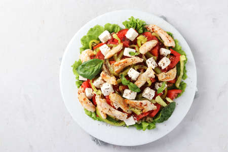 Salad with bulgur, baked chicken, bell pepper, basil and feta on a white plate, top view Reklamní fotografie
