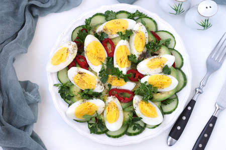 Healthy salad with avocado, cucumbers, eggs and sweet pepper in plate on white background. View from above, Closeup