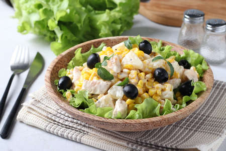Salad with pineapple, baked chicken, corn and black olives on a plate of coconut, Closeup