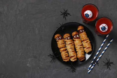 Spooky sausage mummies and tomato juice for Halloween party on dark plate, Top view. Flat lay. Space for text.