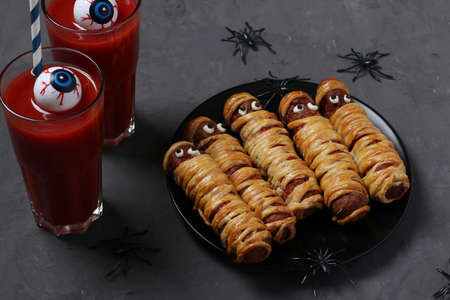 Spooky sausage mummies and tomato juice for Halloween party on dark plate. Funny food idea for kids.