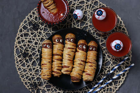 Spooky sausage mummies, tomato juice and sauce for Halloween party on dark background. Top view. Flat lay.