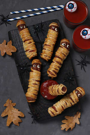 Spooky sausage mummies, tomato juice and sauce for Halloween party on dark wooden board. Top view. Flat lay. Vertical format.