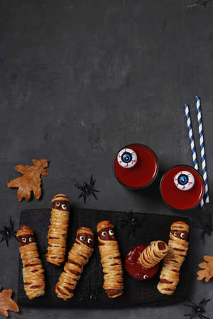 Spooky sausage mummies, tomato juice and sauce for Halloween party on dark wooden board. Top view. Space for text. Vertical format.