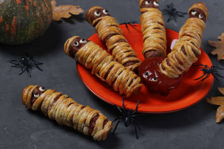 Spooky sausage mummies in dough with ketchup for Halloween party served on dark gray table, Closeup Reklamní fotografie