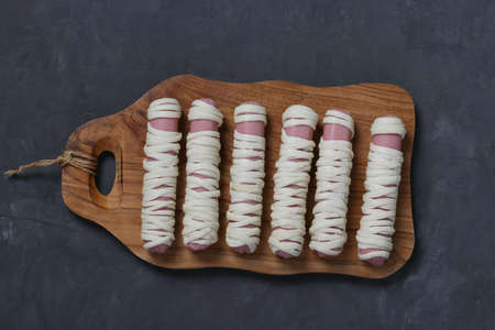 Sausage mummies in dough before baking. Food for Halloween on wooden board. Cooking idea for kids. Top view